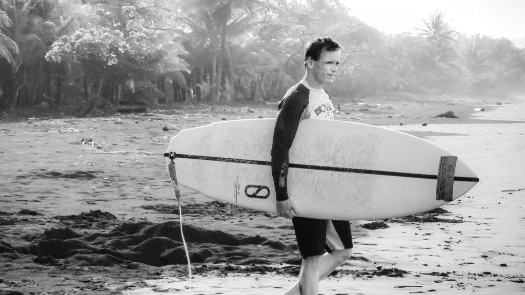 Ned photo black and white with surfboard return guest