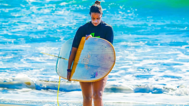Kalon Surf Girl Walking at the beach with surfboard